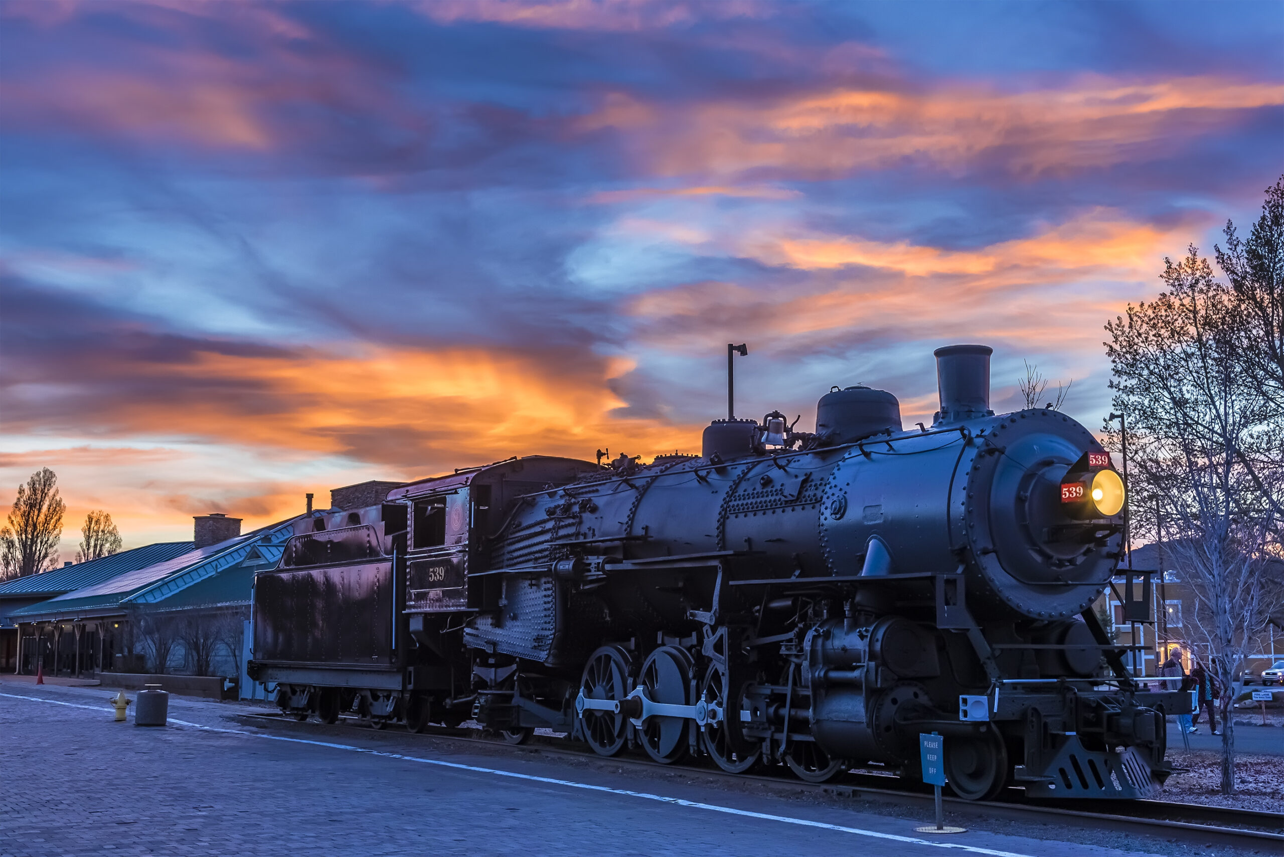 The train to the Grand Canyon waiting at Williams Station, Arizona illuminated by a fiery sunset sky.